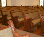 custom upholstered pews, stained wood pew ends, customized carved sides